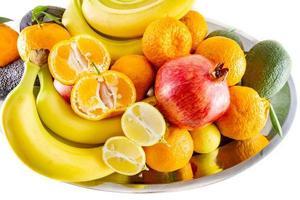 fuente variada de frutas y verduras de plátanos, granada, limón, mandarina y aguacate foto