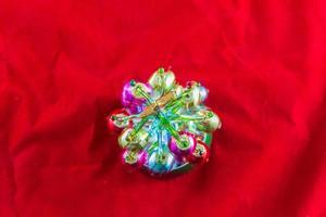 Mini árbol de Navidad de vidrio iluminado y contra un fondo rojo. foto