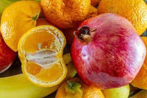 Arreglo de frutas variadas de plátanos, granada, rodajas de limón y rodajas de mandarina foto