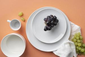 uvas en un plato sobre fondo naranja foto