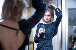 Attractive young woman drinking at the mirror photo