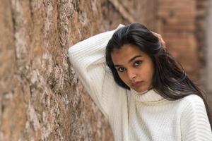Vista frontal retrato de una mujer morena pensativa y contemplativa con la mano en el cabello mirando a la cámara foto