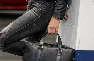 Cropped image of a stylish woman holding a big black leather bag photo