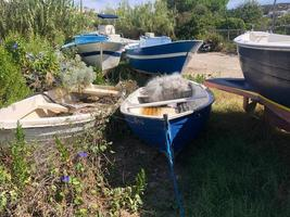 Empty and abandoned fishing boats decaying in a grassy field photo