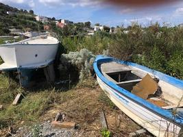 Abandoned and empty fishing boats decaying in a grassy field photo