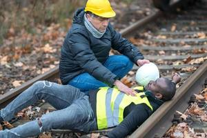 African American railroad engineer injured in an accident at work on the railway tracks photo