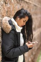 Beautiful brunette young woman in winter clothes using her smartphone listening to music with earphones photo