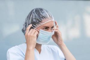 Doctora poniéndose su mascarilla facial foto