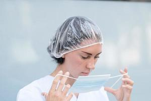 Woman doctor putting on her facial mask photo