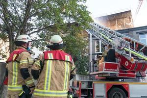 Bomberos en el trabajo extinguiendo el fuego con una escalera giratoria foto