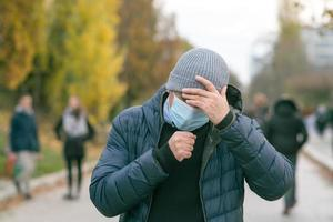 Coughing using a protective mask photo