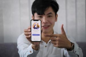 chiang mai, tailandia, 23 de enero de 2021 - hombre apuntando a un teléfono con equipos de microsoft en él foto