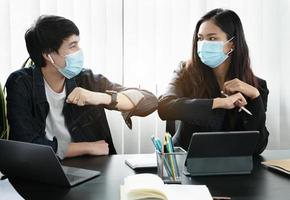 Two professionals bumping elbows with masks on photo