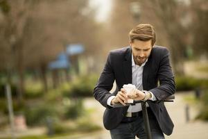 Businessman with coffee cup checking time on electric scooter photo