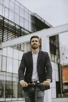Business man riding an electric scooter by an office building photo