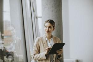 Woman holding tablet in modern office photo