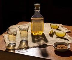 tragos de mezcal o tequila con rodajas de limón foto