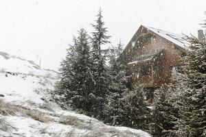 vista de cabaña de troncos nevados foto