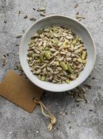 Mezcla de diferentes semillas para una ensalada saludable, cuenco sobre un fondo de hormigón gris foto