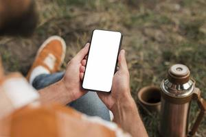 hombre sosteniendo teléfono inteligente mientras acampa al aire libre. concepto de fotografía hermosa de alta calidad y resolución foto