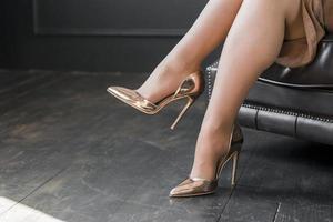 piernas femeninas perfectas con tacones dorados sentado en el sofá. concepto de fotografía hermosa de alta calidad y resolución foto