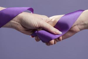 women hands holding purple satin ribbon. High quality and resolution beautiful photo concept
