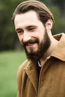 hombre sonriente con un abrigo marrón foto