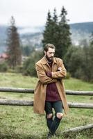 man in a brown coat and torn trousers photo