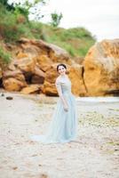 bride in a blue light dress walking along the ocean photo