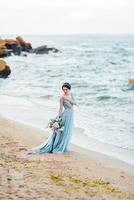 bride with a bouquet of flowers on the beach photo