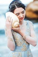 bride with a big shell on the beach photo
