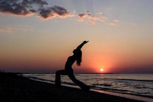 girl on the beach at dawn in yoga assana photo