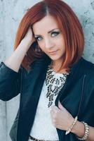 red haired girl in a black jacket and blue glasses photo