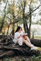 young girl in white clothes sits on a tree in the forest photo
