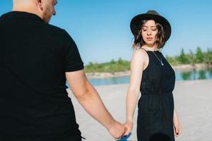 Pareja joven un chico con una chica vestida de negro están caminando sobre la arena blanca foto