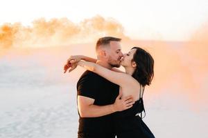 chico y una chica vestidos de negro se abrazan y corren sobre la arena blanca foto