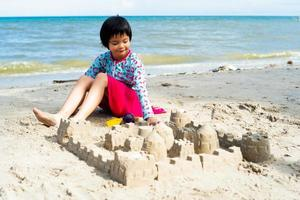 Portrait of Asain girl playing in the sand with toys and building a sandcastle. photo
