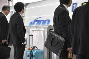 Tokyo, Japan November 4, 2014 - Group of businessmen stand at the platform of a bullet train station and waiting for the departure time during rush hour photo