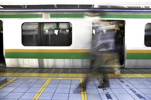 Tokyo, Japan - November 13, 2014 -  The motion of passengers walking on the platform of JR station during rush hour in Tokyo, Japan photo