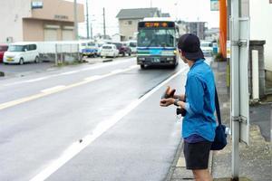 Retrato posterior del turista masculino no identificado esperando el autobús que viene en la parada del autobús. foto