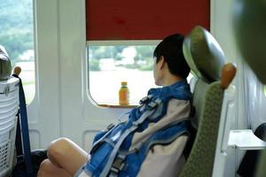 Portrait of Asian man napping during traveling by train. A man sits on the window seat of a train. photo