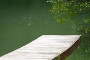 Selective focus on a wooden bridge with blurred branches of tree and lake in the background. photo