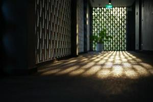 Selective focus on the cement floor of corridor reflecting light of sunset with blurred bokeh lights background. photo