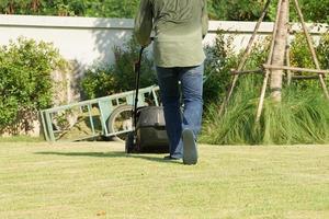 Retrato posterior del jardinero empujando la cortadora de césped en el campo de hierba foto
