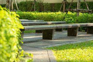 Selective focus of empty concrete benches in an outdoor park with blurred green bush in the background photo
