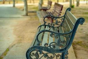 Close up of rusted steel bench with blurred wooden benches in the background at an outdoor public park photo