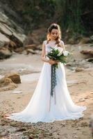 novia con un ramo de novia en la orilla del mar foto