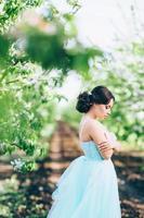 Chica morena con un vestido turquesa en el jardín de primavera foto