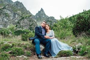 pareja joven en un paseo cerca del lago rodeado por las montañas foto