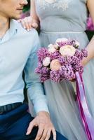 un chico y una chica caminan en el jardín de primavera de lilas foto